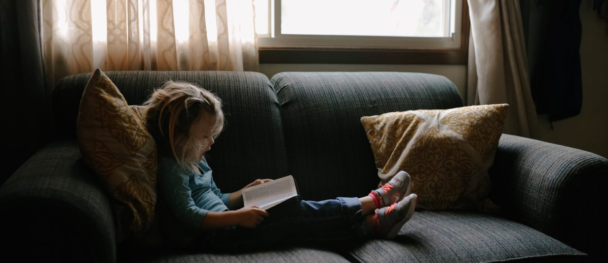 photo of small child reading on a couch