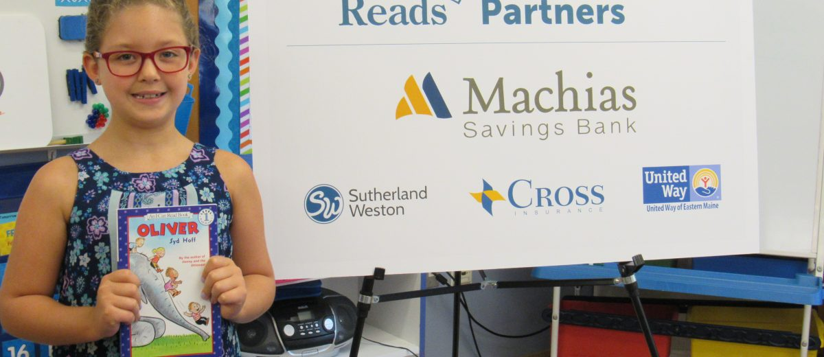 photo of first grader holding a book with a dirigo reads thanks to our partners poster