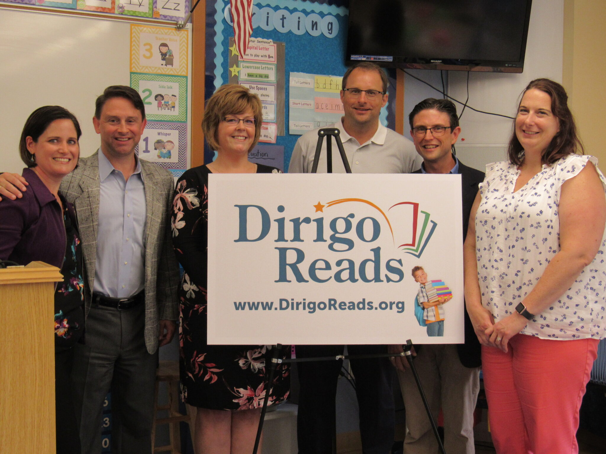 photo of dan and karen cashman with partners behind a dirigo reads poster